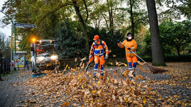 Businessfotografie - Männer fegen das Herbstlaub zusammen